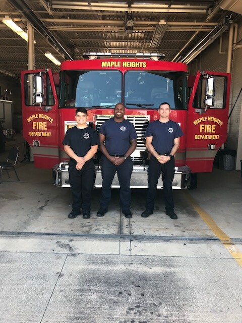 3 new Fire Department cadets standing in front of a Maple Heights fire engine